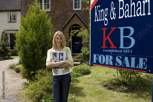 Young woman with magazine outside house with 'for sale' sign, smiling, portrait