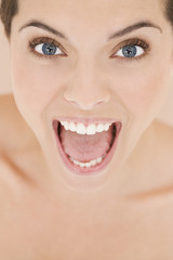 Portrait of young woman with mouth open wide, screaming