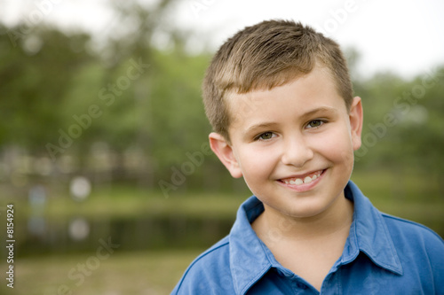 portrait boy smiling standing in park