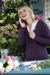 Woman florist taking an order over the telephone