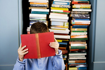little boy hiding behind a book