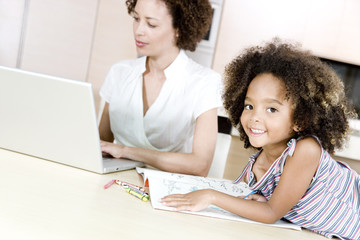 Mother typing on a laptop while young daughter looks at a colouring book