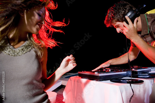 Young woman dancing by the DJ