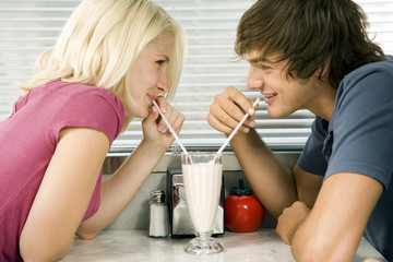 Teenage couple sharing a milkshake