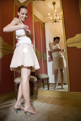 Woman trying on clothes in the changing room of a high-class shop, checking the price