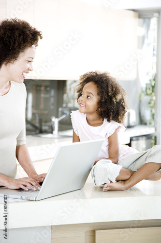 Mother using laptop in kitchen while young daughter looks on smiling