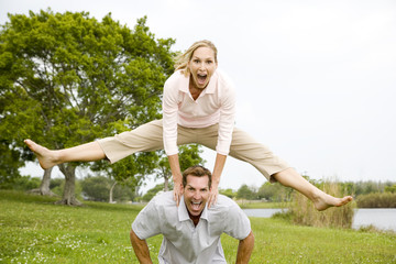mid adult couple playing leapfrog