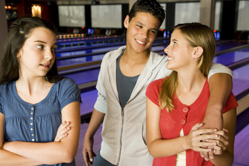 Teenage couple in a bowling alley, watched by jealous rival