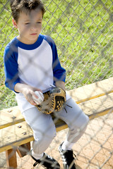 Boy in baseball gear sitting on a bench
