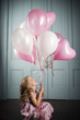 little girl sitting on the floor looking up at her bunch of balloons
