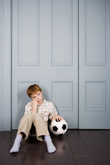 sad little boy sitting on floor with football