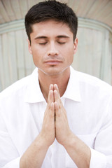Portrait of a man with dark hair, meditating