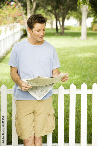 man reading paper in the garden
