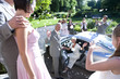 Wedding party throwing confetti on senior bride and groom waving from car, elevated view