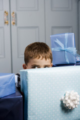 little boy hiding behind pile of presents