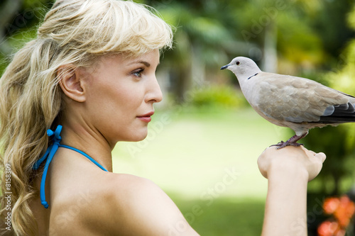 Portrait of a woman in a tropical setting with a dove on her hand.