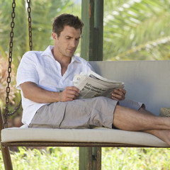 A man reading a newspaper on a swing