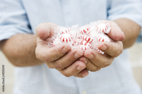 Senior man's hand holding sweets or candy