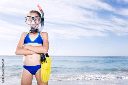 A young girl in snorkeling gear on the beach