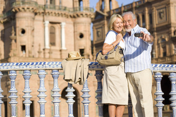 Senior couple taking photograph of themselves by castle