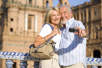 Senior couple taking photograph of themselves by castle, close-up