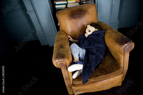 little boy curled up asleep in armchair