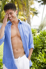 Portrait of man in tropical setting, shirt open