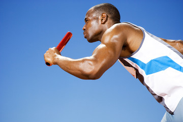 Relay runner with baton in his hand