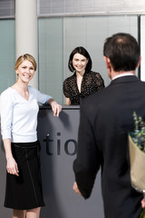 Businessman with bouquet of flowers being greeted by two women at office reception