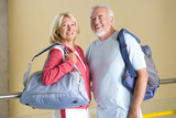 Senior couple by railing with gym bags, smiling, portrait
