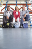 Two senior men and woman with gym bags sitting on steps, smiling, portrait