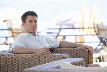 A man relaxing with a drink on holiday
