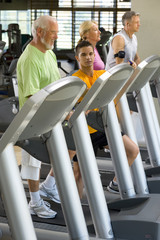 Senior man on treadmill with personal trainer