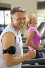 Mature man in gym with earphones, smiling, portrait