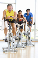 People on exercise bicycles in gym, low angle view
