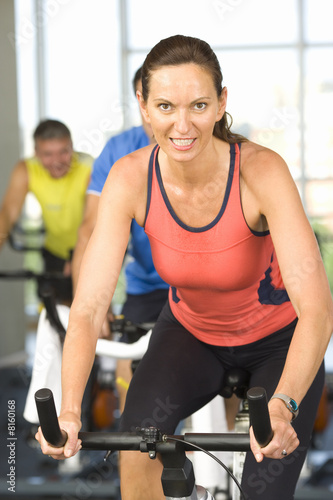 Woman on exercise bicycle, smiling, portrait