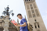 Male tourist looking at book by tower, low angle view