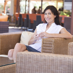 A woman relaxing with a drink on holiday