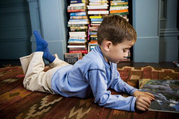 little boy reading picture book lying on the floor