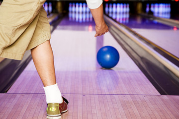 Teenage boy in a bowling alley, rolling the ball