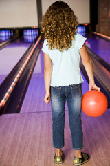 Girl in a bowling alley holding a red bowling ball