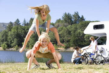 Girl (9-11) jumping over brother (10-12) on grass, parents by motor home in background