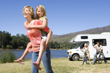 Girl (9-11) on mother's back, father and brother (10-12) by motor home in background