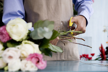 Male florist creating a bouquet of flowers, cutting the stems
