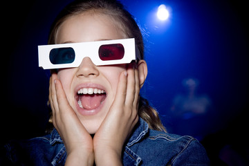 Girl at the cinema watching a film through 3-D glasses