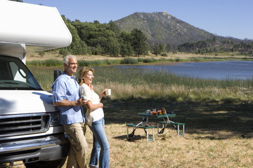 Mature couple with mugs by motor home by lake, side view
