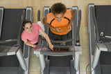 Fitness instructor training man on treadmill in gym, portrait, elevated view