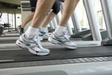Man running on treadmill, close-up of feet, low section