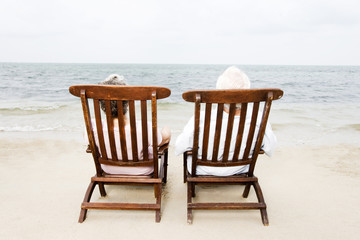 Senior couple relaxing in wooden steamer chairs at the beach