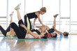 Female fitness instructor teaching class in studio in gym, hand on man's leg, portrait of man smiling